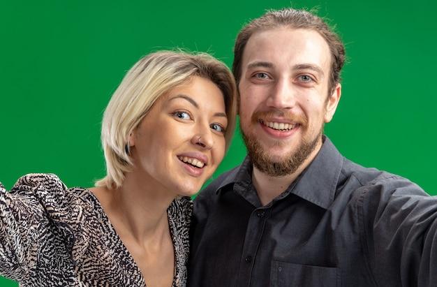 緑の壁の上に立ってバレンタインデーを広く祝って幸せで陽気な笑顔のカメラを見て若い美しいカップルの男性と女性