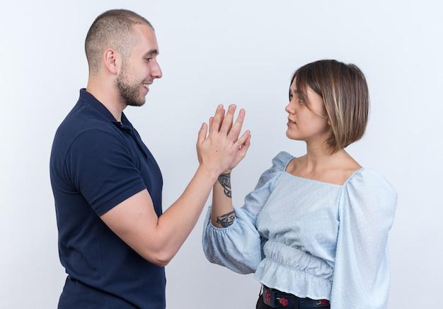 행복하고 자신감이 서있는 손으로 만지고 서로를보고 젊은 아름 다운 부부 남자와 여자