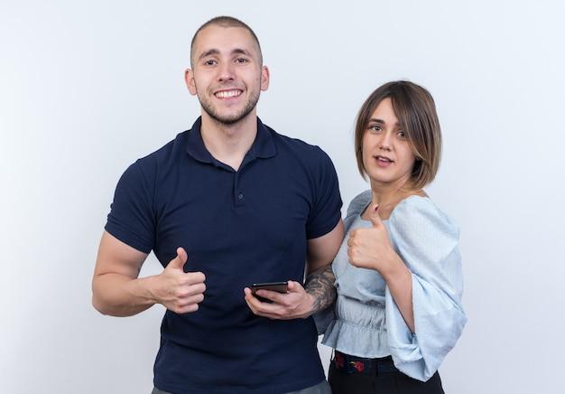 若い美しいカップルの男と女が幸せで肯定的な笑顔を見て、立っている親指を陽気に表示