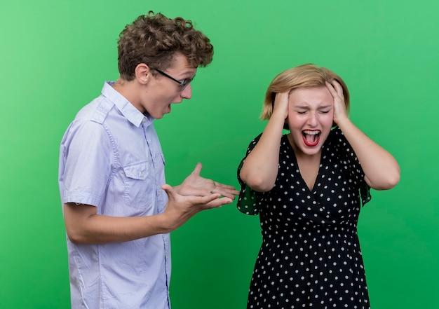 젊은 아름 다운 부부 남자와 여자는 녹색 벽 위에 서 서로 비명 싸움