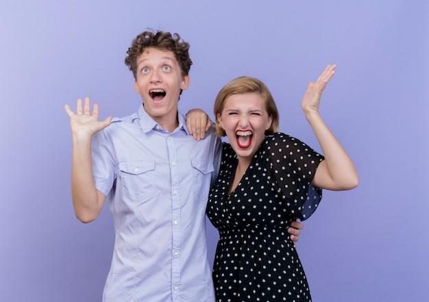 젊은 아름 다운 부부 남자와 여자는 파란색 벽에 행복 하 고 흥분 기뻐