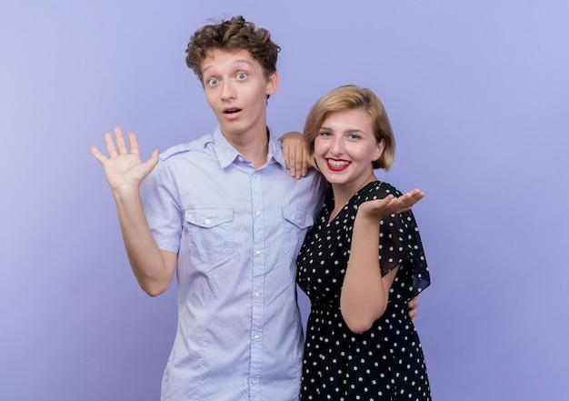 若い美しいカップルの男性と女性の笑顔と青い壁の上に立っている側に腕を広げて