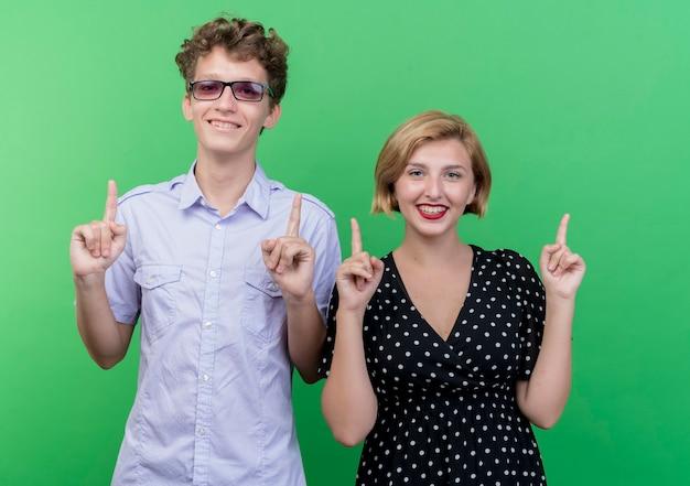 젊은 아름 다운 부부 남자와 여자는 녹색 벽 위에 서 검지 손가락으로 행복하고 긍정적 인 pointign 미소