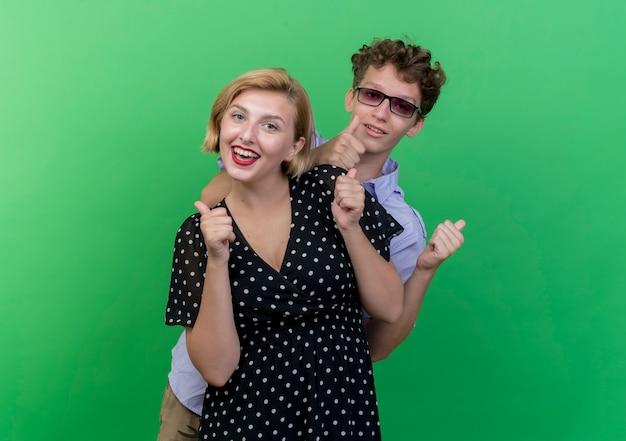 Молодая красивая пара мужчина и женщина улыбаются счастливым и позитивным, показывая пальцы вверх, стоя над зеленой стеной