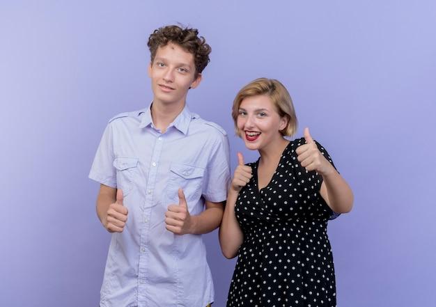 Молодая красивая пара мужчина и женщина улыбается, показывая пальцы вверх, стоя над синей стеной
