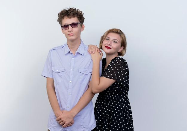Молодая красивая пара мужчина и женщина улыбается женщина обнимает своего парня, стоящего над белой стеной