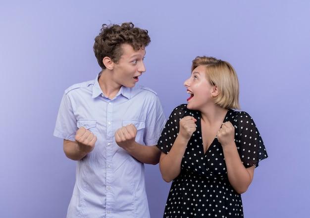 파란색 벽에 행복하고 흥분 주먹을 떨림 서로 옆에 서있는 젊은 아름 다운 부부 남자와 여자