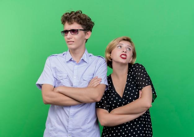 젊은 아름 다운 부부 남자와 여자는 녹색 벽 위에 서 혼란 찾고 서로 옆에 서