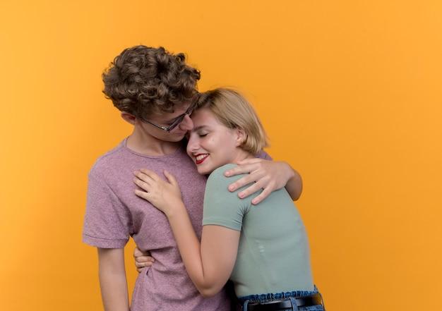 Молодая красивая пара мужчина и женщина, стоящие вместе счастливы в любви, обнимаются, стоя над оранжевой стеной