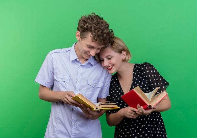 젊은 아름 다운 부부 남자와여자가 함께 책을 들고 서 행복 하 고 긍정적 인 녹색 벽 위에 서 웃 고