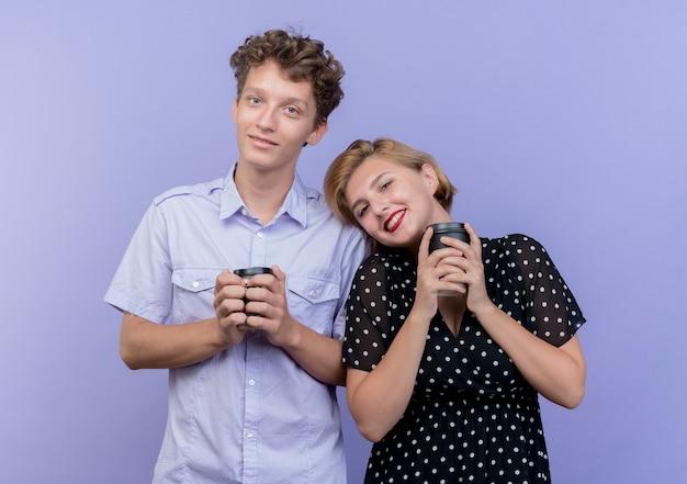 青い壁の上に元気に立って笑顔のコーヒーカップを持って一緒に立っている若い美しいカップルの男性と女性