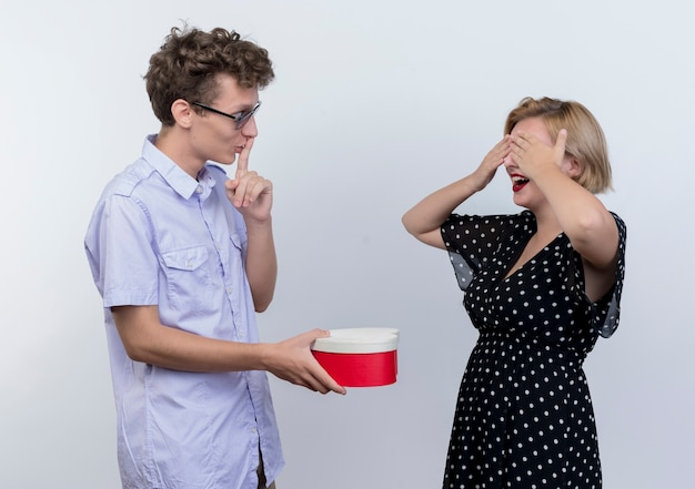 彼女が白い壁に目を閉じている間、若い美しいカップルの男性と女性が一緒に立っている男性は彼のガールフレンドに驚きを作っています
