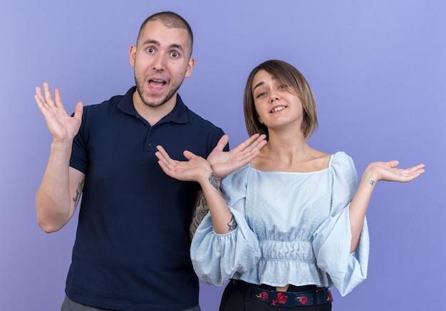 若い美しいカップルの男と女は、青い壁の上に立って、陽気に笑みを浮かべて両側に腕を広げて驚いた