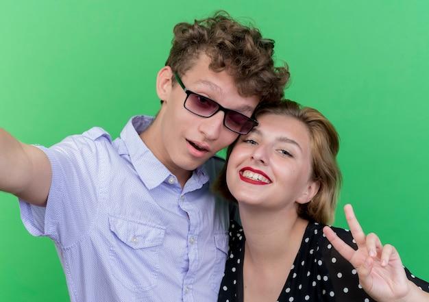 젊은 아름 다운 부부 남자와 여자 복용 selfie 행복 하 고 긍정적 인 녹색 벽 위에 v 기호 서 표시