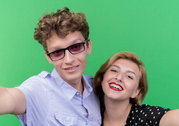 젊은 아름 다운 부부 남자와 여자 복용 selfie 행복 녹색 벽 위에 광범위하게 서 웃 고