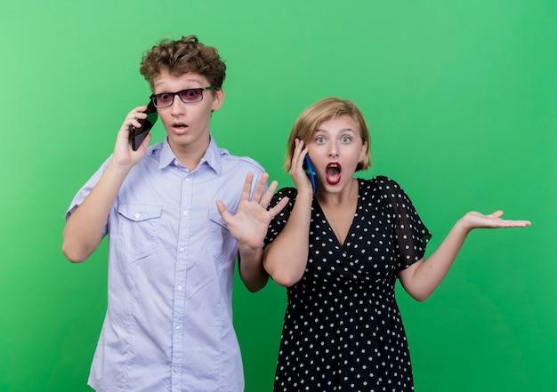 젊은 아름 다운 부부 남자와 여자는 녹색 벽 위에 혼란과 불확실한 서를 찾고 휴대 전화에 얘기