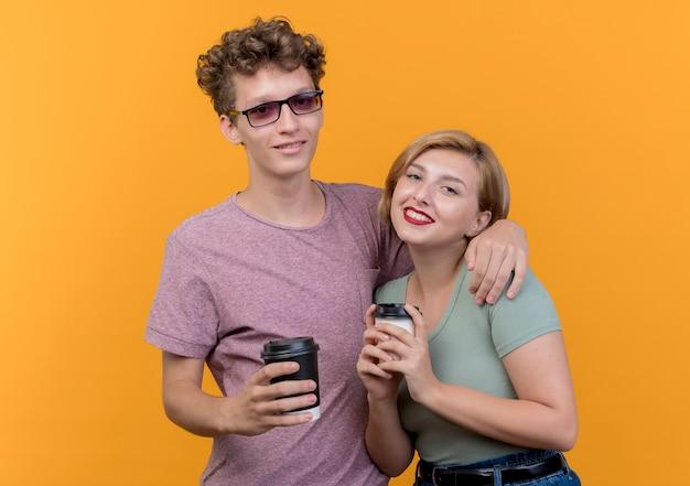 オレンジ色の上に元気に笑ってコーヒーカップを保持しているカジュアルな服を着ている若い美しいカップルの男性と女性