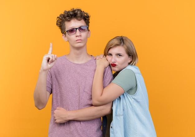 그의 여자 친구가 오렌지 벽 위에 서 불쾌한 동안 검지 손가락을 보여주는 캐주얼 옷 남자를 입고 젊은 아름 다운 부부 남자와 여자