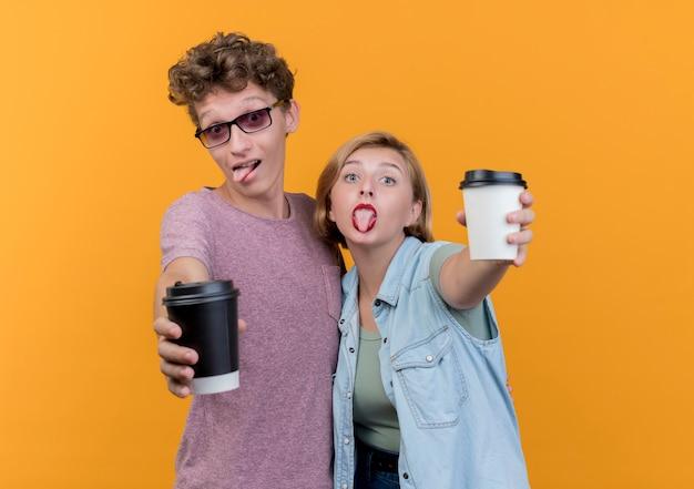 オレンジ色の壁の上に立っている舌を突き出してポーズと笑顔のコーヒーカップを示すカジュアルな服を着ている若い美しいカップルの男性と女性
