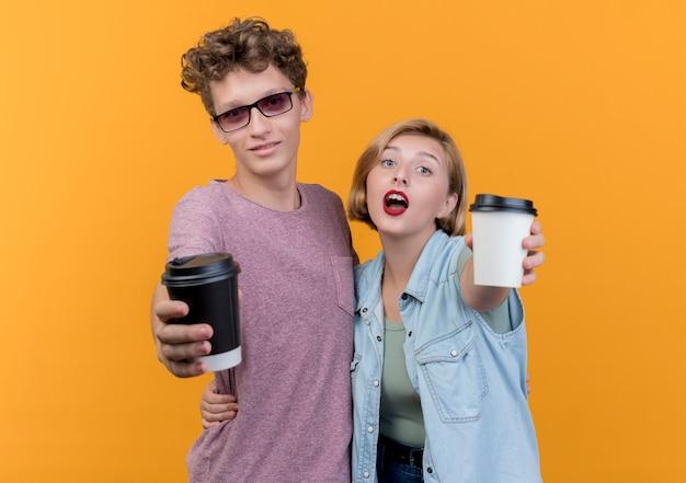 オレンジ色の壁の上に立って笑顔のコーヒーカップを示すカジュアルな服を着ている若い美しいカップルの男性と女性