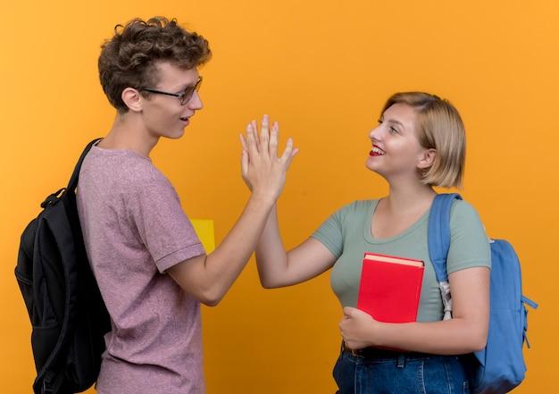 オレンジ色の壁に笑顔を与えるハイタッチを与える向かい合って立っているカジュアルな服を着ている若い美しいカップルの男性と女性