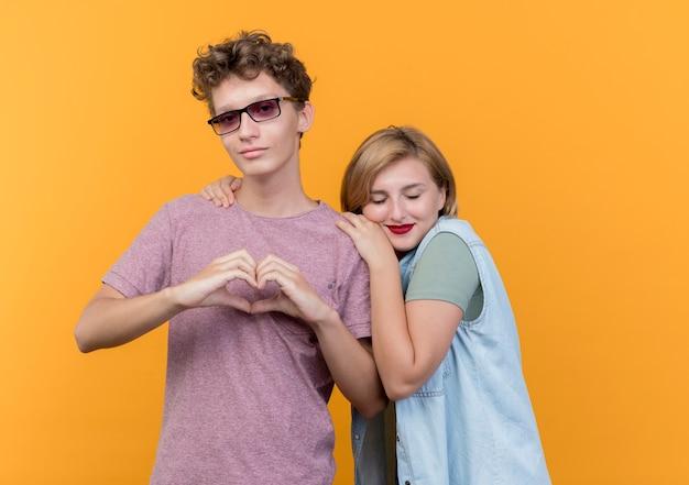 젊은 아름 다운 부부 남자와여자가 함께 서있는 캐주얼 옷을 입고 그의 gilfriend가 오렌지 벽에 그의 어깨에 그녀의 머리를 기대하는 동안 심장 제스처를 보여주는 남자