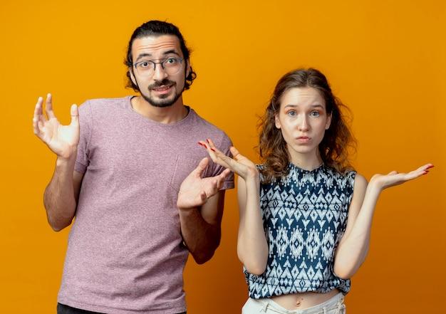 Молодая красивая пара мужчина и женщина в замешательстве и неуверенности, не имея ответа, раскинув руки в стороны, стоя над оранжевой стеной