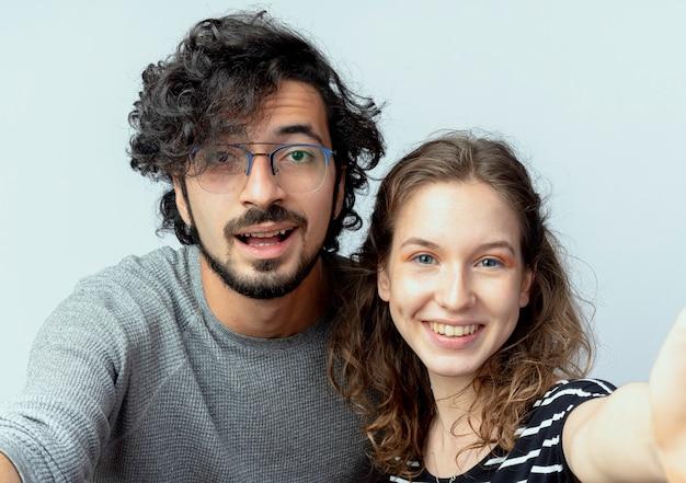 젊은 아름 다운 부부 남자와 여자는 흰색 배경 위에 카메라를 유쾌 하 게보고 웃 고 사랑에 행복