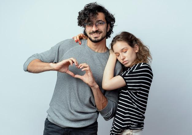 若い美しいカップルの男性と女性は恋に幸せ、彼は白い壁の上で幸せで前向きな指でハートジェスチャーをしながら彼女のボーイフレンドを抱き締める女性