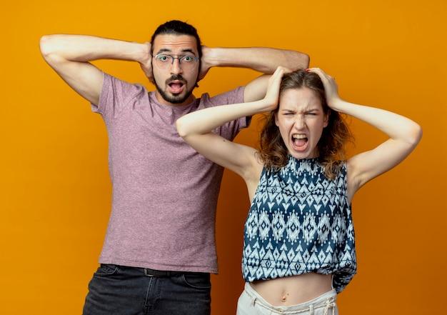 젊은 아름 다운 부부 남자와 여자는 카메라를보고 혼란과 오렌지 배경 위에 서있는 머리를 만지고 좌절