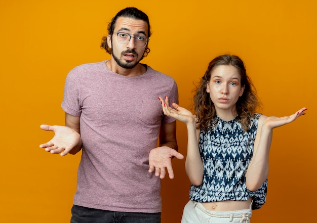 カメラを見ている若い美しいカップルの男性と女性は混乱し、オレンジ色の背景の上に立っている側に腕をスプレイディング答えがない不確かです