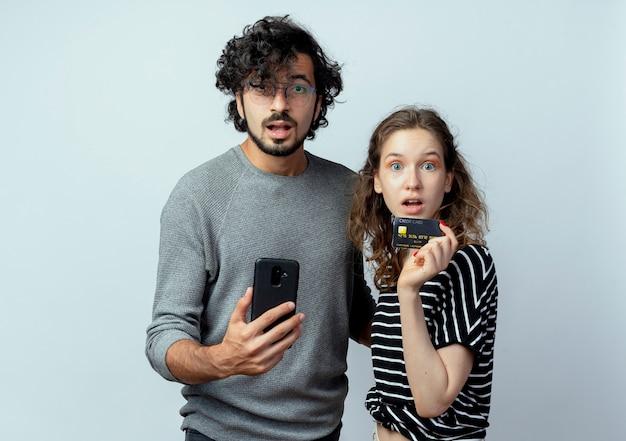 젊은 아름 다운 부부 남자와 여자는 흰색 배경 위에 신용 카드를 들고 그의 여자 친구 옆에 서 스마트 폰을 들고 카메라 혼란 남자를 찾고
