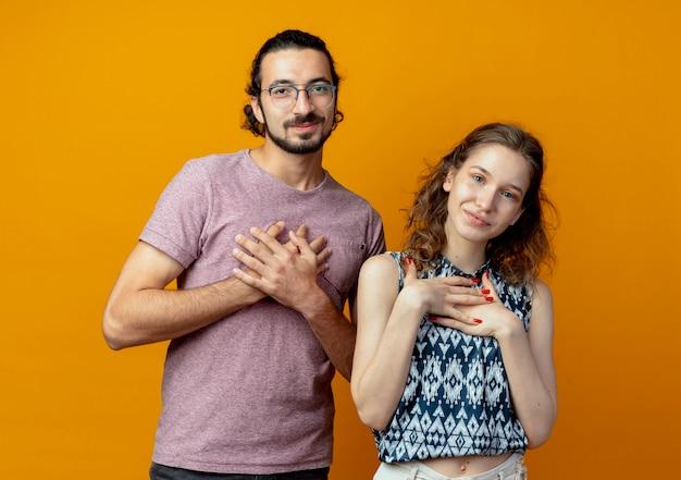 オレンジ色の背景の上に立って感謝を感じて彼の胸に手をつないでカメラを見ている若い美しいカップルの男性と女性