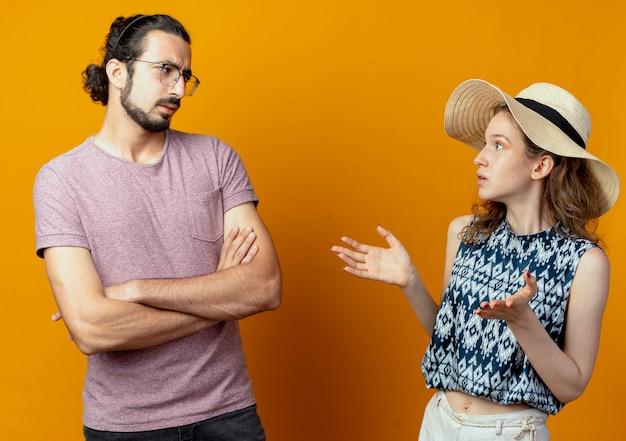 オレンジ色の壁の上に立っている眉をひそめている顔でお互いを見て喧嘩し、身振りで示す若い美しいカップルの男性と女性