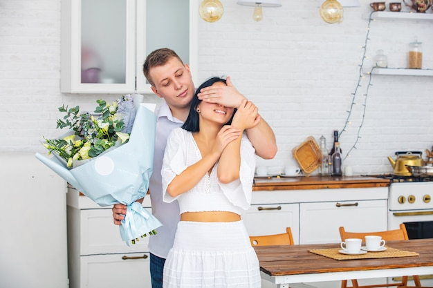 Young beautiful couple a man gives a woman flowers for a holiday at home