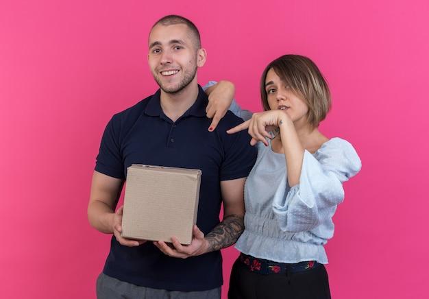 Giovane bella coppia che tiene in mano una scatola di cartone mentre la sua ragazza indica con l'indice la scatola in piedi