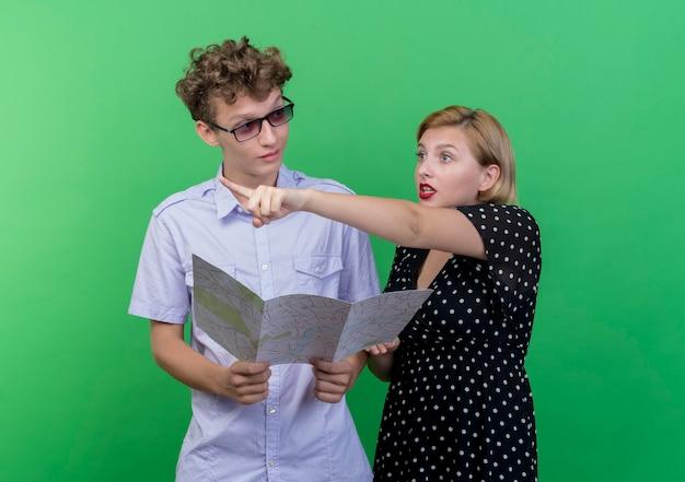 Молодая красивая пара мужчина держит карту, глядя на свою смущенную подругу, которая указывает на что-то пальцем, стоящим над зеленой стеной