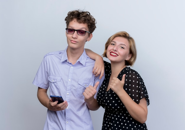 Молодая красивая пара мужчина держит смартфон, пока его девушка с улыбкой показывает палец вверх, стоя над белой стеной