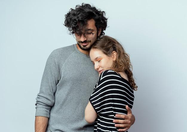 Молодая красивая пара мужчина обнимает свою любимую подругу, стоя на белом фоне