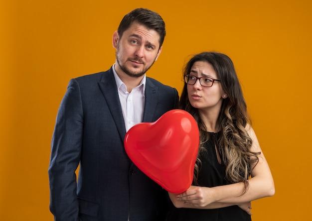 Giovane e bella coppia uomo e donna risentita con palloncino rosso a forma di cuore in piedi uno accanto all'altro per celebrare il giorno di san valentino