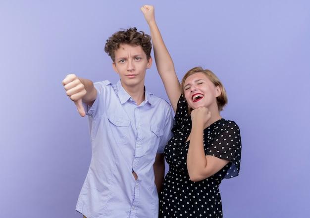 그의 여자 친구가 파란색 벽에 행복하고 흥분하는 동안 아래로 엄지 손가락을 보여주는 젊은 아름 다운 부부 남자