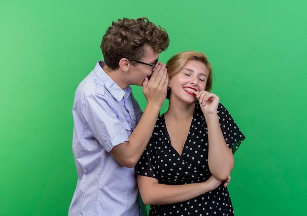 Giovane bella coppia uomo che bisbiglia un segreto alla sua ragazza sorridente in piedi sopra la parete verde