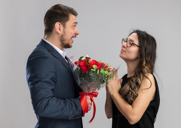 Молодая красивая пара мужчина с букетом роз, глядя на свою довольную и счастливую подругу, счастливую в любви, празднует день святого валентина над белой стеной