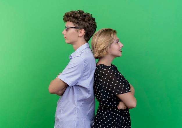 Giovane bella coppia uomo e donna schiena contro schiena aggrottando le sopracciglia sul verde