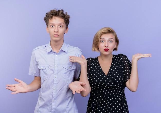 Giovane bella coppia uomo e donna confuso scrollare le spalle non avendo risposta in piedi sopra la parete blu