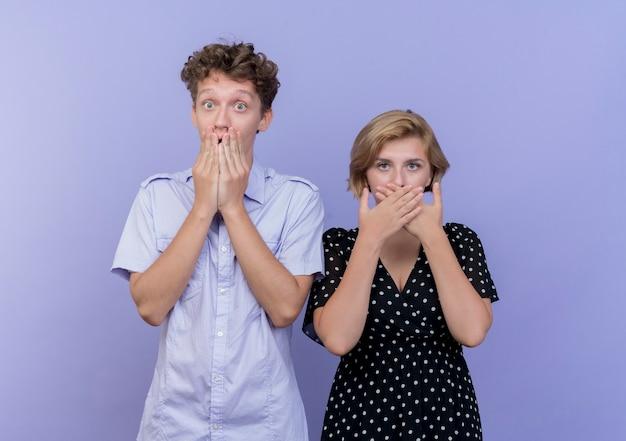 Giovane bella coppia uomo e donna che copre la bocca con le mani scioccate in piedi sopra la parete blu