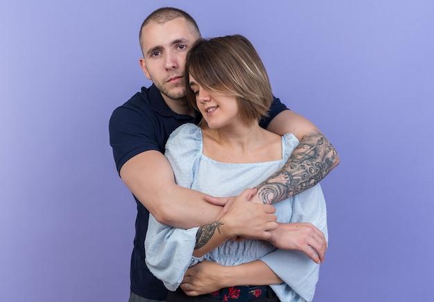 Giovane bella coppia uomo e donna che si abbracciano felici innamorati insieme sorridenti in piedi sul muro blu