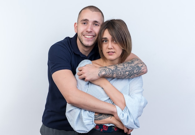Giovane bella coppia uomo e donna che abbraccia felice e positivo sorridente in piedi sul muro bianco