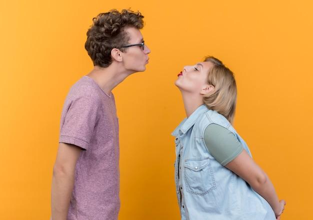 Giovane bella coppia uomo e donna felice innamorato mantenendo le labbra come per baciarsi in piedi sopra il muro arancione
