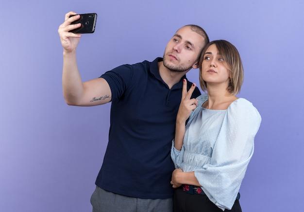 Giovane bella coppia uomo e donna felice e positiva che fa selfie insieme usando lo smartphone che mostra il segno v in piedi sopra la parete blu
